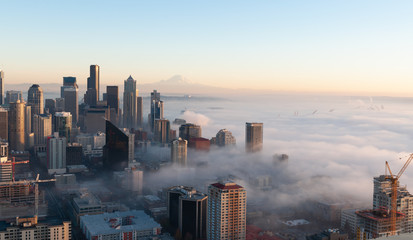 Partially immersed in the fog from Elliott Bay, this panoramic view of Seattle at sunset,in a cold autumn day, with blue sky and the Mount Rainier visible on the background. Wall mural