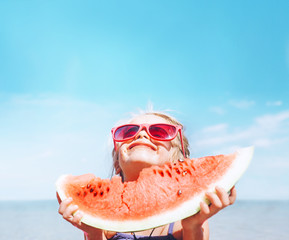 Little girl in pink sunglasses with big watermelon segment funny portrait. Healthy eating concept image.