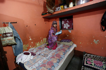 Aisha, a law student, holds the Koran after reading it inside her house in village Nayabans