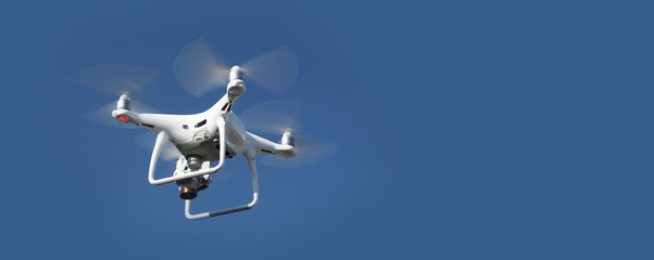 Drone on blue sky background. Remote control quadrocopter with camera for photography. Flying robot.