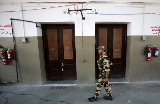 A member of Central Industrial Security Force keeps guard outside sealed strong rooms where electronic voting machines are kept, in Ahmedabad