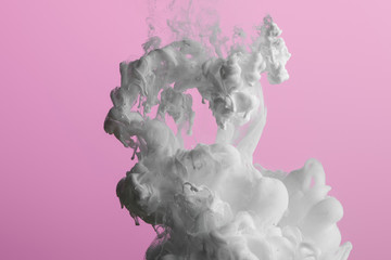 Wall Mural - Close up view of white paint splash isolated on pink