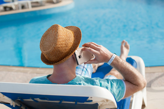 man lying on a lounger and talking on a phone near the pool