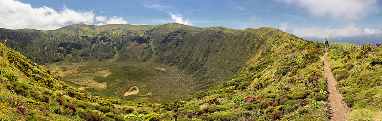 Women is hiking along the crater rim of Caldeira of Faial, Azores