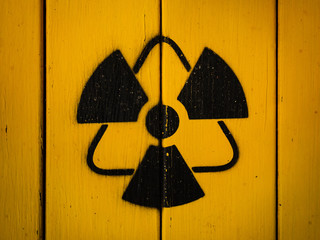 Radioactivity sign, close-up. Sign of radiation on a yellow wooden board. Radioactive sign - symbol of radiation. Yellow and black radioactive hazard, ionizing radiation, nuclear danger warning symbol