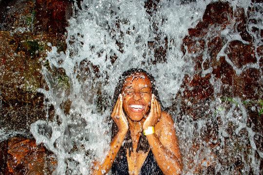 Black Woman Taking Bath From Waterfall