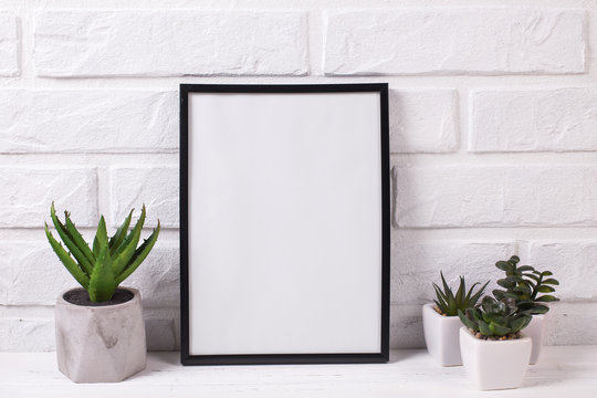 Empty  black frame mockup and succulents and cactus plants