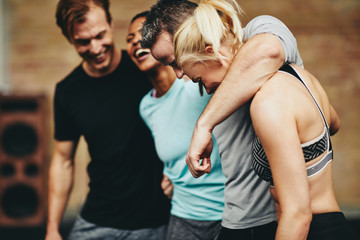 Diverse group of fit friends laughing together at the gym