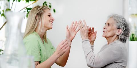 Seniorin und Pflegerin spielen
