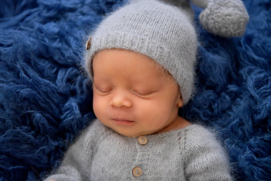 Sleeping newborn boy in the first days of life on blue background