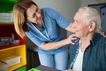Fototapeta Happy caretaker assisting senior man. Friendly nurse supporting old man with Parkinson's Disease obraz