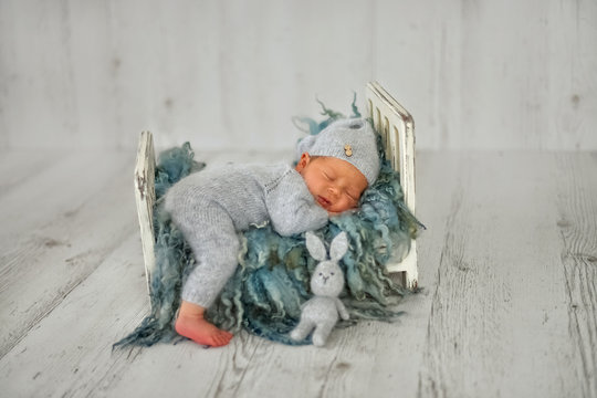 A newborn baby boy is sleeping on a little cot in the first days of life