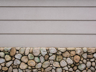 Picture of white concrete wall with stones at the basement and vertical several lines