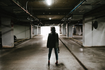 Young brunette woman posing on the underground parking lot. Woman in the parking lot.