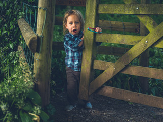 Little toddler opening wooden gate in the woods