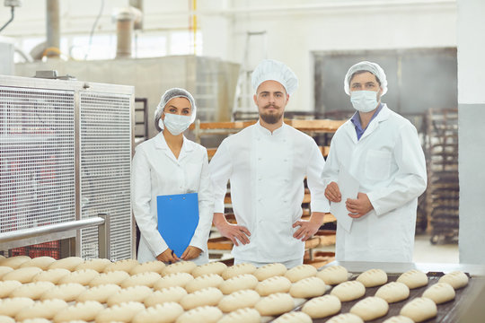 Technologist and baker inspect the bread production line at the bakery