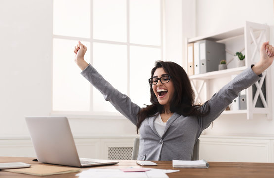 Excited Businesswoman Celebrating Success With Raised Hands At Workplace
