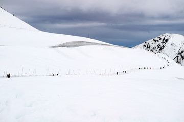People walk on the road on top of higher mountain, Landscape view of hill that cover with snow