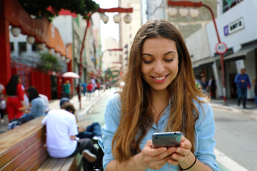 Portrait of a smiling young woman walking in the Sao Paulo City with cellphone, Brazil