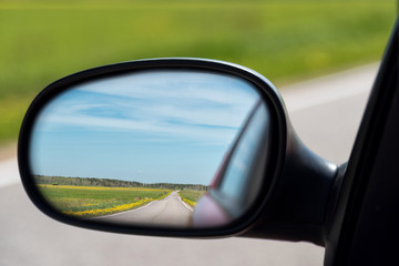 View of the highway in the side mirror of the car. Distance traveled.