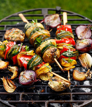 Vegetarian skewers, grilled vegetable skewers of zucchini, peppers and potatoes with the addition of aromatic herbs and olive oil on the grill outdoors. Grilled food