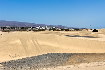 Maspalomas,Gran Canaria - The sand dunes in famous natural area and the village in  background . Canary Islands, Spain