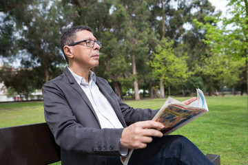 Relaxed man reading newspaper and sitting on bench in park. Guy wearing casual clothes and sitting with green lawn and trees in background. News and nature concept.