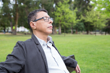 Relaxed middle-aged man sitting on bench in park. Guy wearing casual clothes and keeping his eyes closed with green lawn and trees in background. Relaxation and nature concept.