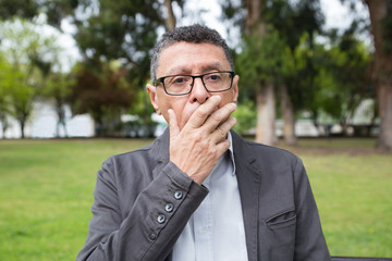 Shocked middle-aged man covering mouth with hand in park. Guy wearing casual clothes and standing with green lawn and trees in background. Shock and nature concept. Front view.