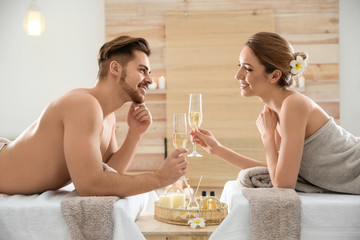 Romantic young couple with champagne in spa salon Fototapete