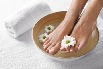 La pose en embrasure Pedicure Closeup view of woman soaking her feet in dish with water and flowers on white towel, space for text. Spa treatment