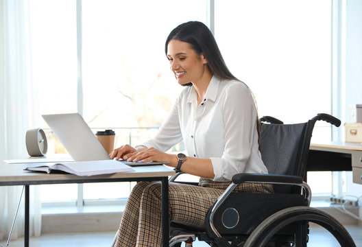 Young woman in wheelchair using laptop at workplace