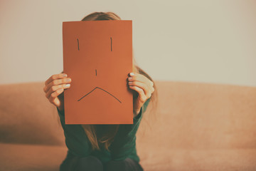 Depressed woman sitting alone at sofa and holding paper with sad face.Toned image.