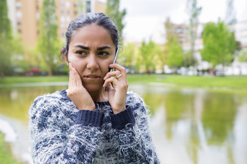 Worried young woman talking on smartphone in city park. Pretty lady wearing sweater, touching face and standing with blurred pond, green trees and buildings in background. Problem concept. Front view.