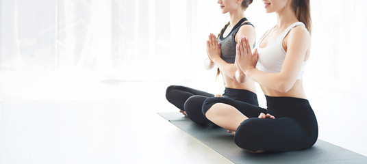 Two young women in yoga class making exercises