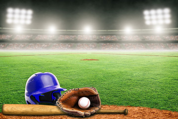 Baseball Helmet, Bat, Glove and Ball on Field in Outdoor Stadium With Copy Space