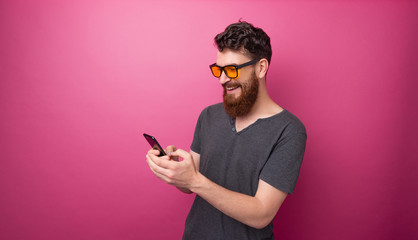 Photo pf stylish bearded man using a mobile phone, pink isolated background Wall mural
