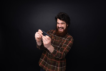 Excited bearded guy playing on mobile over dark wall background
