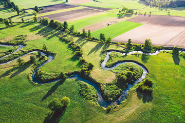 Foto op Canvas Rivier A winding river surrounded by green meadows