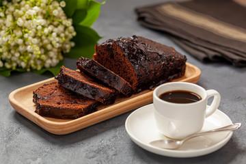 Ciasto czekoladowe na drewnianej tacce, kawa, konwalie i ścierka kuchenna