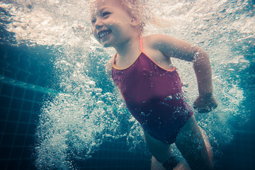 Happy child toddler swimming underwater in swimming pool
