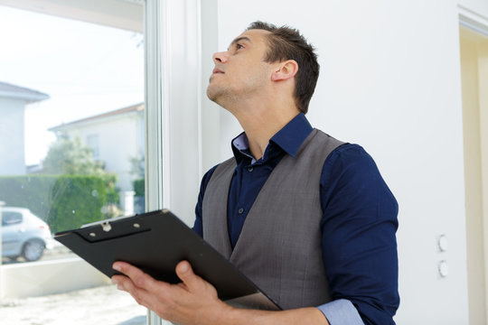 estate agent inspecting window in property