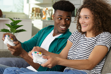 happy couple sitting on sofa playing video games