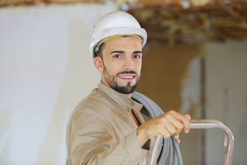 man in hard hat with ladder