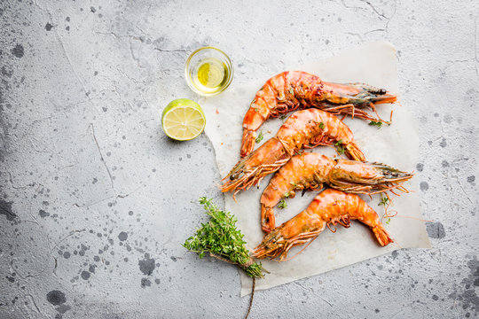 Grilled giant tiger prawns on paper with lemon and spices on light gray background, top view, copy space. Seafood dinner.