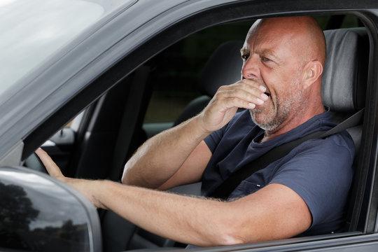 man yawning in car during traffic jam