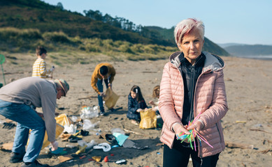 Serious woman showing handful of straws collected on the beach with group of volunteers working in the background. Selective focus in woman in foreground