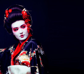 young pretty real geisha in kimono with sakura and decoration on black background