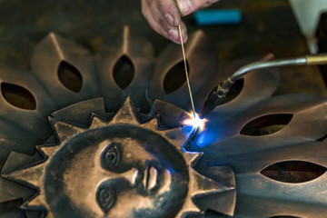 Work gas burner welds decorative copper parts, sun