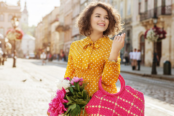 Outdoor portrait of young beautiful happy smiling lady wearing stylish yellow polka dot dress, holding straw wicker bag with peonies, walking in street of European city. Copy, empty space for text